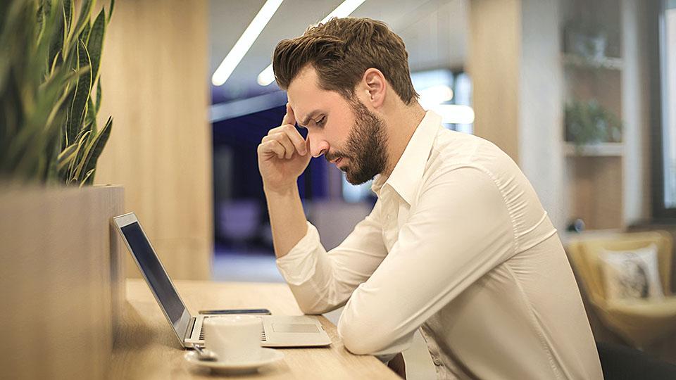 Mann beugt sich konzentriert über Laptop