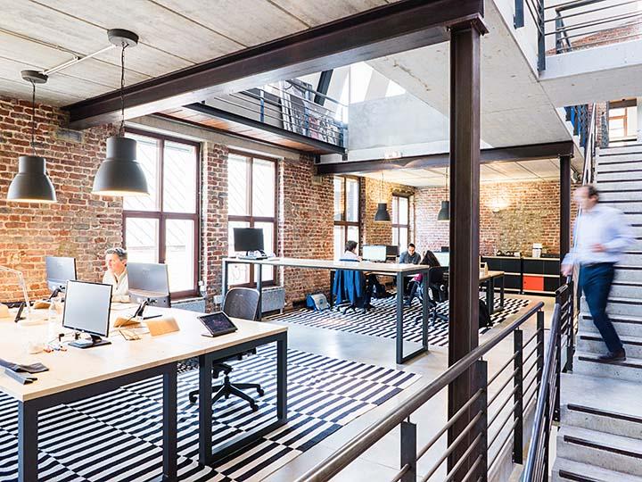 Grossraumbüro mit Backsteinwänden und grossen Fenstern