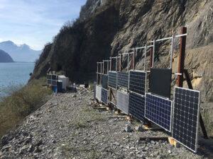 Solarpanels auf Kiesplatz an steilem Hang, links See und Berge