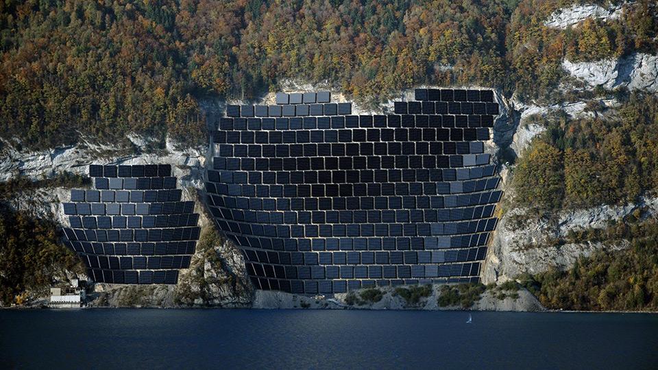 Vollflächig mit Solarpanels ausgekleideter Steinbruch am See