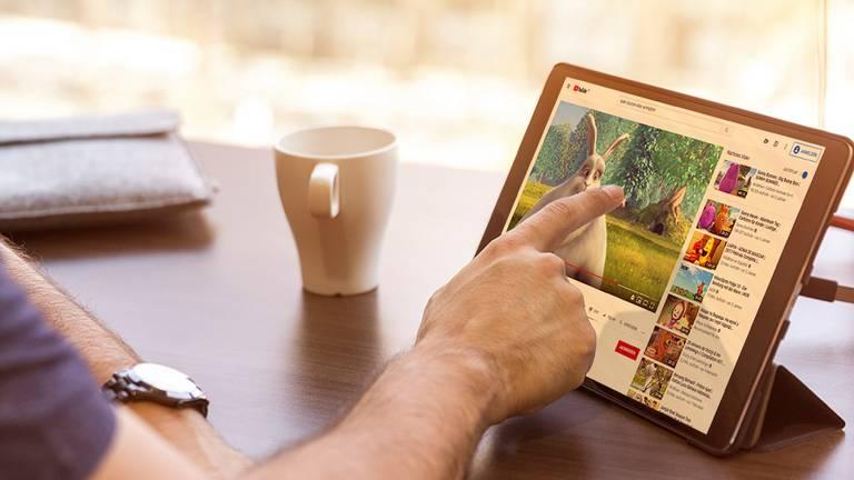 YouTube-Trickfilm auf Tablet mit Tasse nebendran
