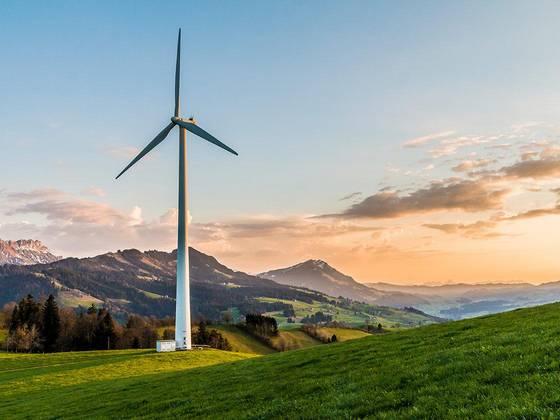 Einzelne Windkraftanlage auf Anhöhe vor rotblauem Himmel