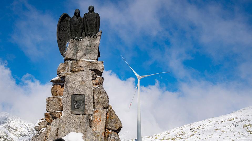 Alpine Windturbine hinter Denkmal mit Adlern
