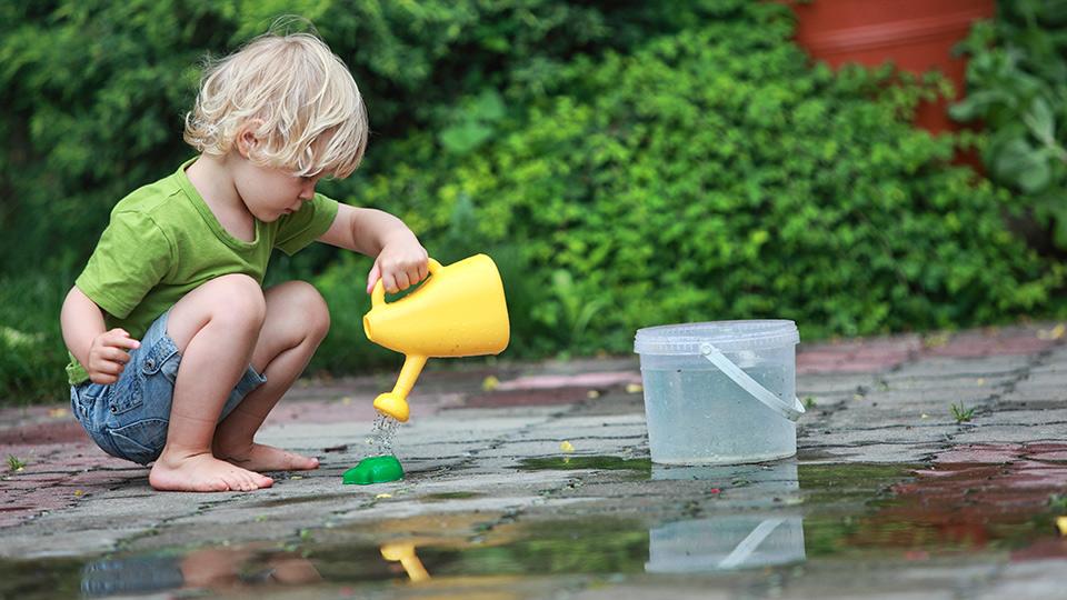 Kind spielt mit Giesskanne an Wasserpfütze