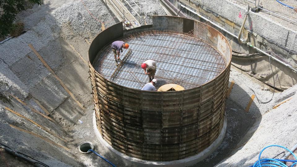 Drei Baufachleute verlegen Armierungseisen in einem runden Bauwerk