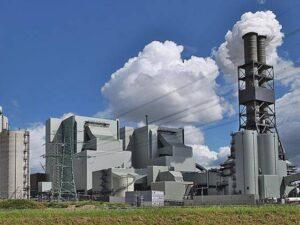 Zwei Kraftwerksblöcke, im Vordergrund ein Kamin mit weissem Rauch