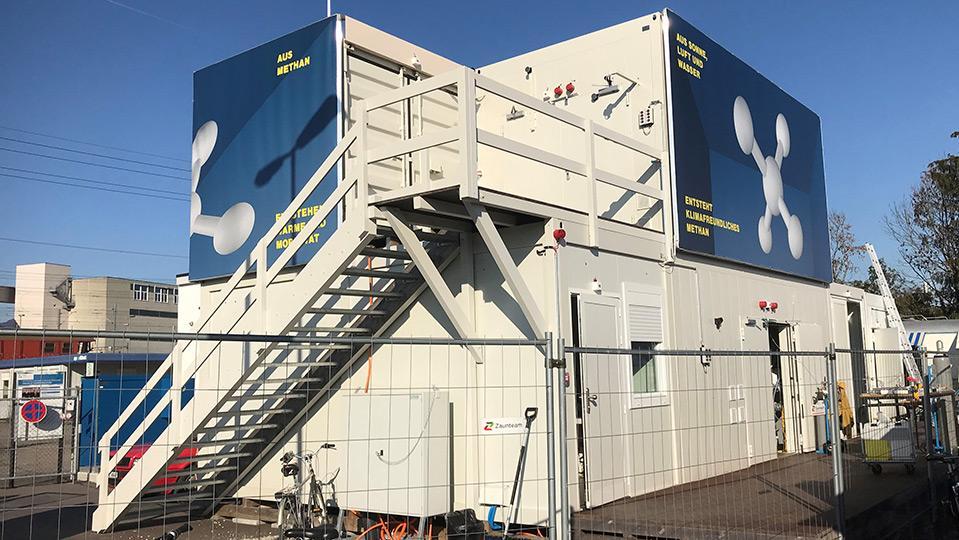 Gestapelte Container mit Power-to-Gas-Plakaten