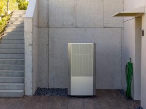 Metallisch glänzende Wärmepumpe mit Lochblech-Front zwischen Treppe und Hauseingang (UG)