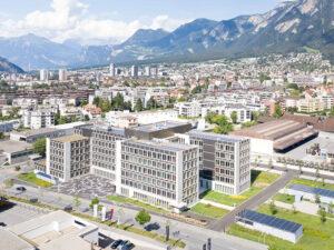 Luftbild eines modernen Gebäudekomplexes, Stadt und Berge im Hintergrund