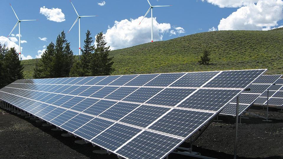 Photovoltaik-Anlage mit Windkrafträdern im Hintergrund