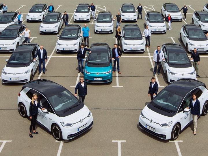 20 ID.3 und ihre Testfahrerinnen und Testfahrer auf Parkplatz