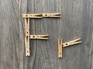 """Wäscheklammern aus Holz bilden die Buchstaben """"Fr""""."""