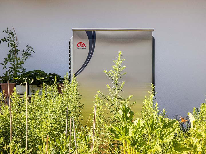 Wärmepumpe inmitten von grünen Pflanzen vor Hauswand